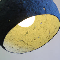 Royal blue eco friendly pendant lamp.  Globe shaped (with the bottom removed) and paper mache (papier-mâché) rough textured finish, showing sporadic holes.  Off-white interior is visible and bulb is glowing.