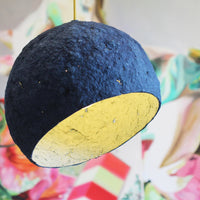 Royal blue environmentally friendly pendant lamp.  Globe shaped (with the bottom removed) and paper mache (papier-mâché) rough textured finish, showing sporadic holes.  Off-white interior is visible.