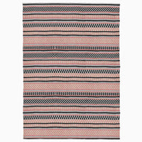 Rectangular rug made from recycled plastic bottles.  It has a coral pink and black stripes, filled with geometric design.