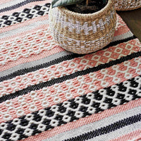 Close up of coral pink striped geometric eco rug.  Sustainably made from recycled plastic bottles and suitable for indoor or outdoor use.  Ethically sourced with GoodWeave.