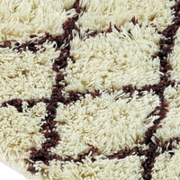 Close up showing shaggy pile of ivory rug with brown diamond shapes.  Made from environmentally friendly recycled plastic bottles.