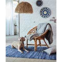 A dog and wooden chair sitting on a blue recycled denim rug.  Sustainable home decor.  Goodweave certification ensures the rug is ethical.