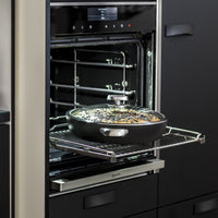 Scanpan Pro IQ 32cm recycled aluminium chef pan with lid, on a rack in the oven.  Contains a rich, saucy meal.