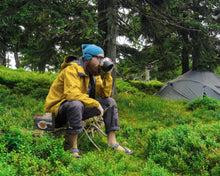 Load image into Gallery viewer, Lightload Puer Tea 1 sitting on rock drinking tea with box next to him-lightload tea