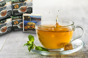 Lightload Puer Tea liguor in a cup with splash next to samplers-lightload tea