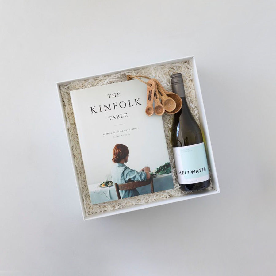 Gift box with recipe book, bottle of wine and wooden measuring spoons