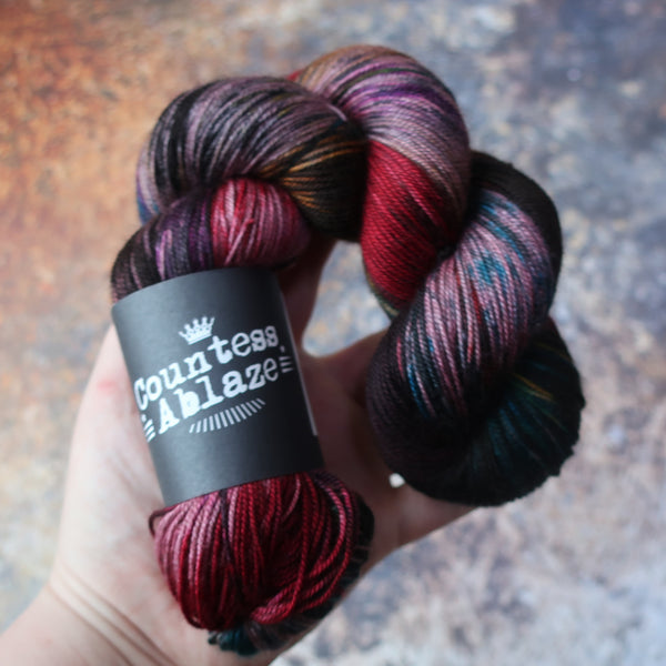 Variegated hand-dyed yarn by Countess Ablaze, 4ply weight merino wool, silk and yak