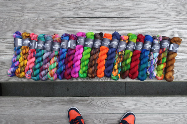 20 colourways of sock yarn on a table with Haydn's sneakers peeking through.