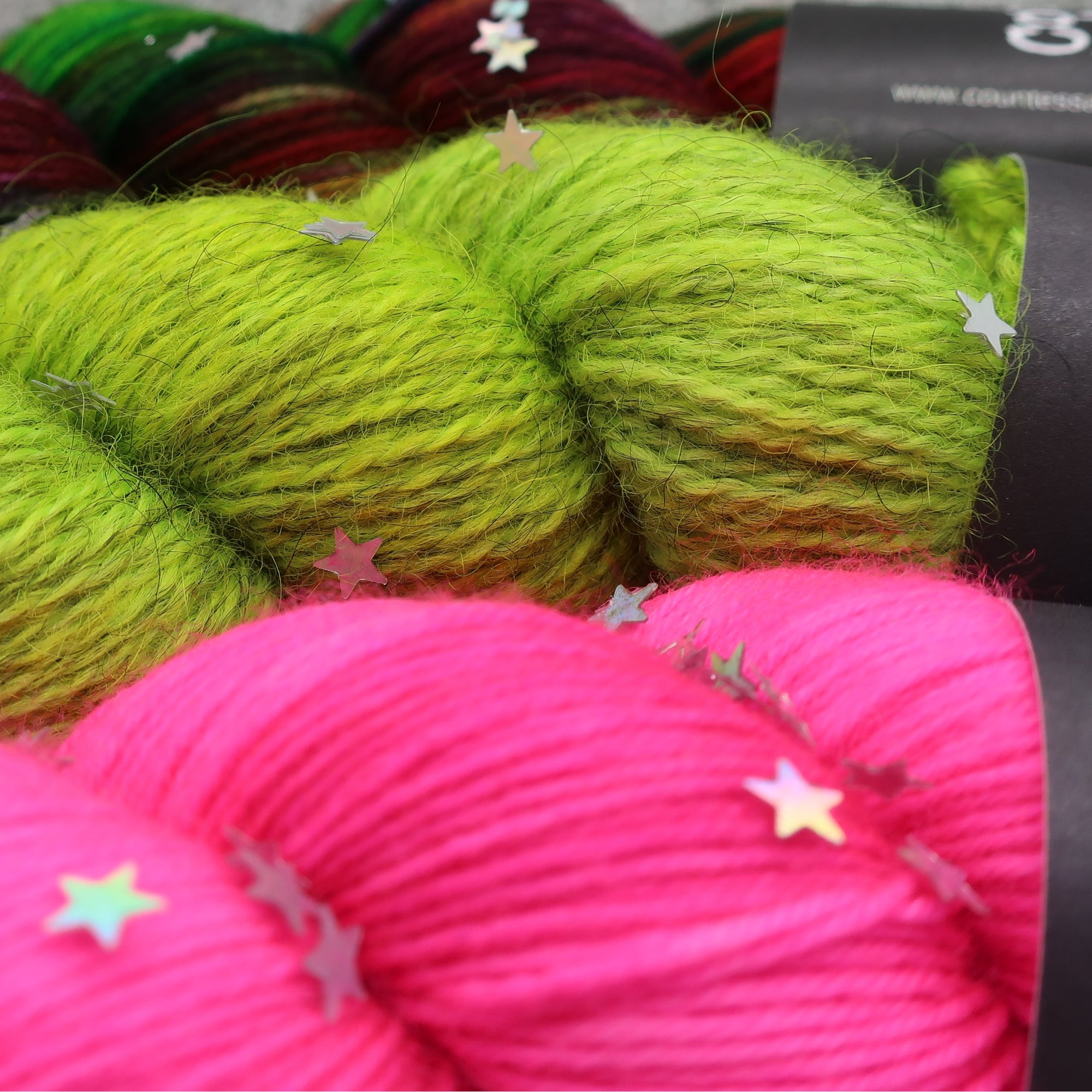Skeins of hand-dyed wool yarn by Countess Ablaze. Merino, Bluefaced Leceister, Gotland wool, sock yarn in green and pink.