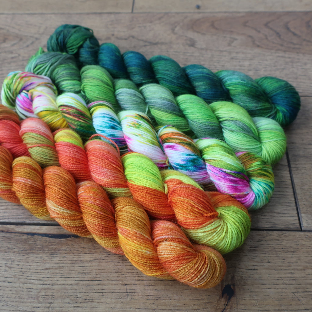 Five skeins of yarn in oranges, speckles and greens.