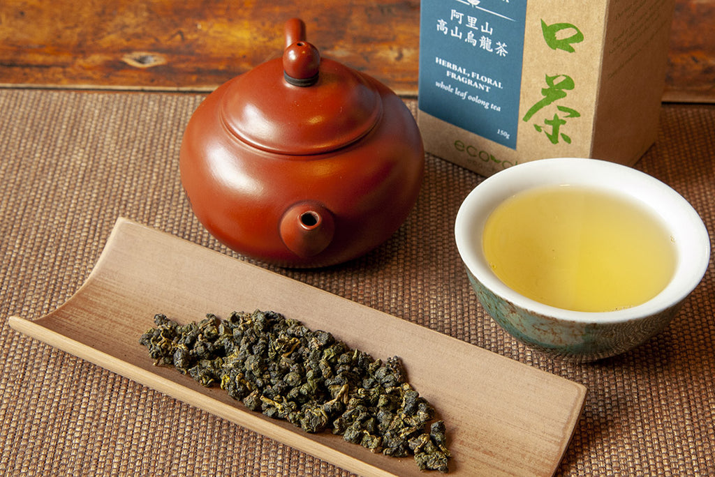 Freshly brewed Oolong Tea alongside dry tea leaves and a pot