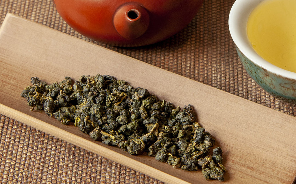 Unroasted Alishan high mountain tea leaves with pot and teacup