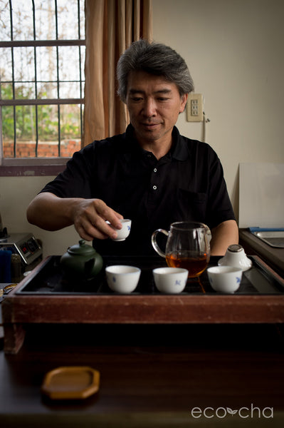 Traditional charcoal-roasted Dong Ding Tea artisan, Mr. Su, serving tea in his home.