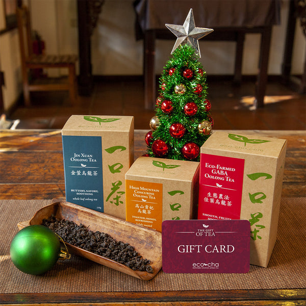 Eco-Cha Gift Card in front of some packaged teas and a small Christmas tree.