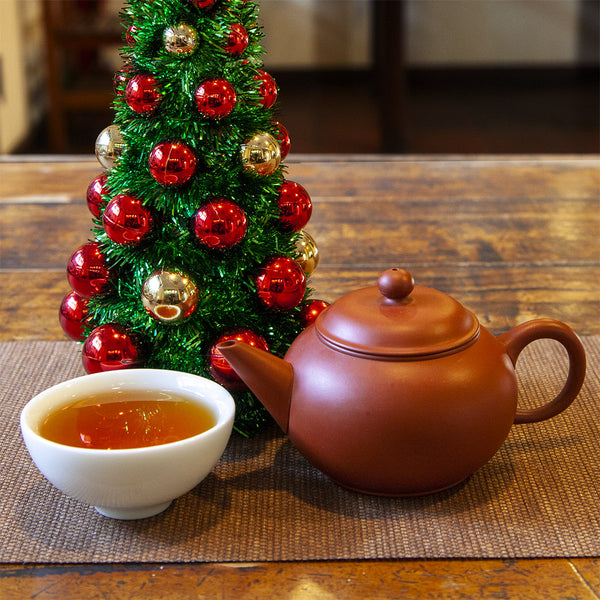 Classic gongfu clay teapot next to a cup of tea in front of a small Christmas tree