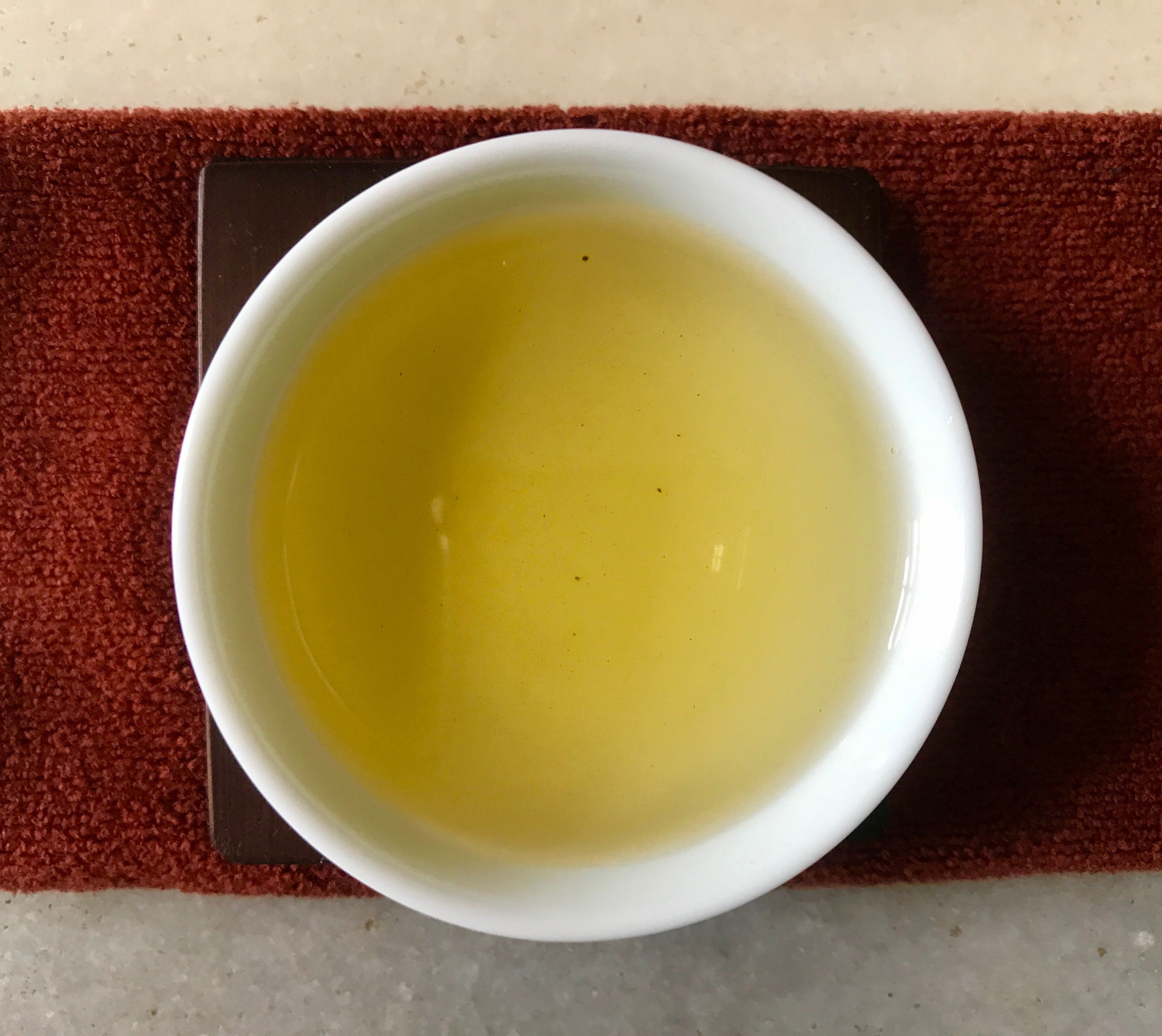 Overhead view of Eco-Farmed Dong Pian Jade Oolong Tea in a tea cup