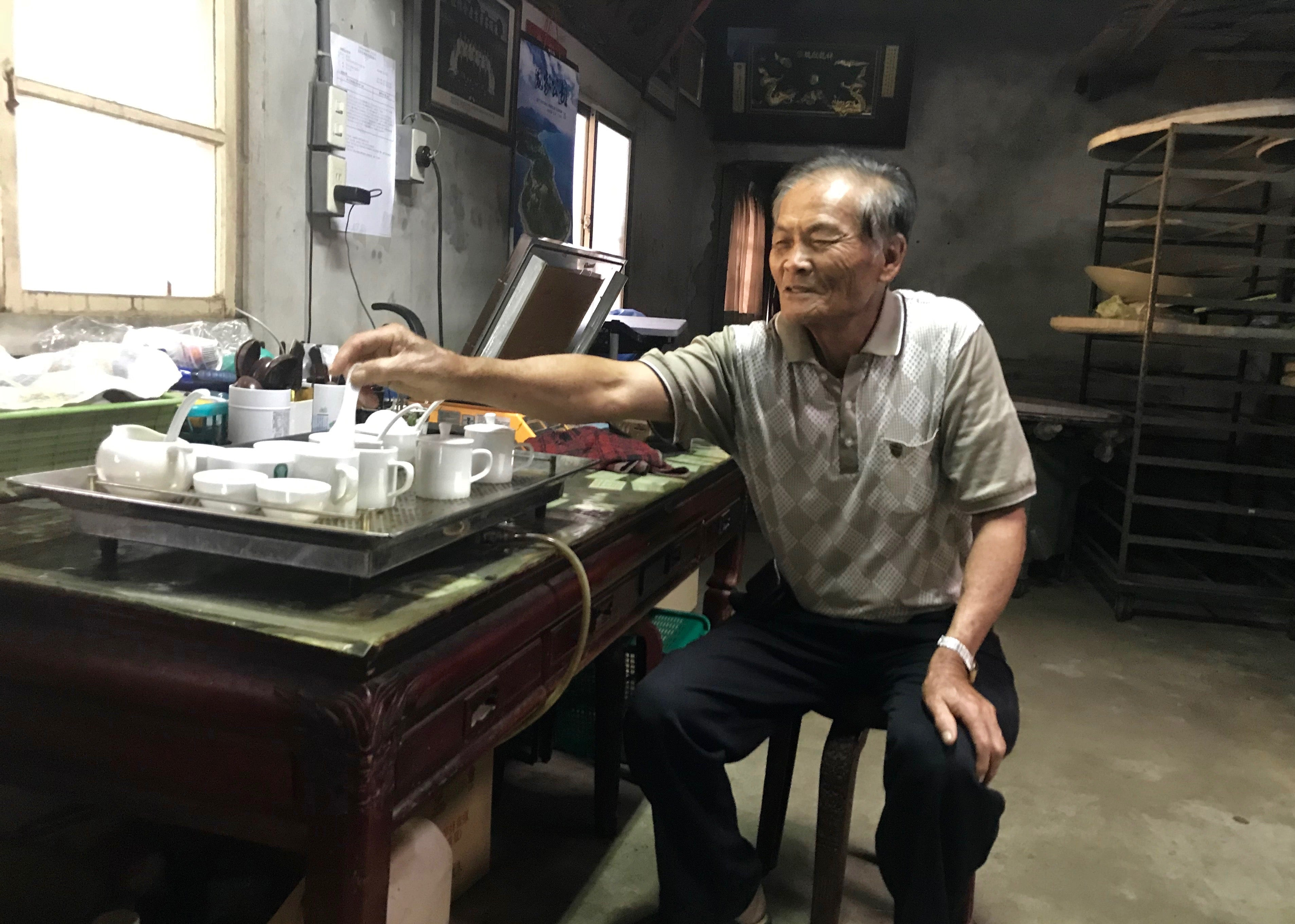 Mr. Su in his workshop tasting the batches of tea that would be delivered to the Farmers' Association the next day for the winter tea competition.