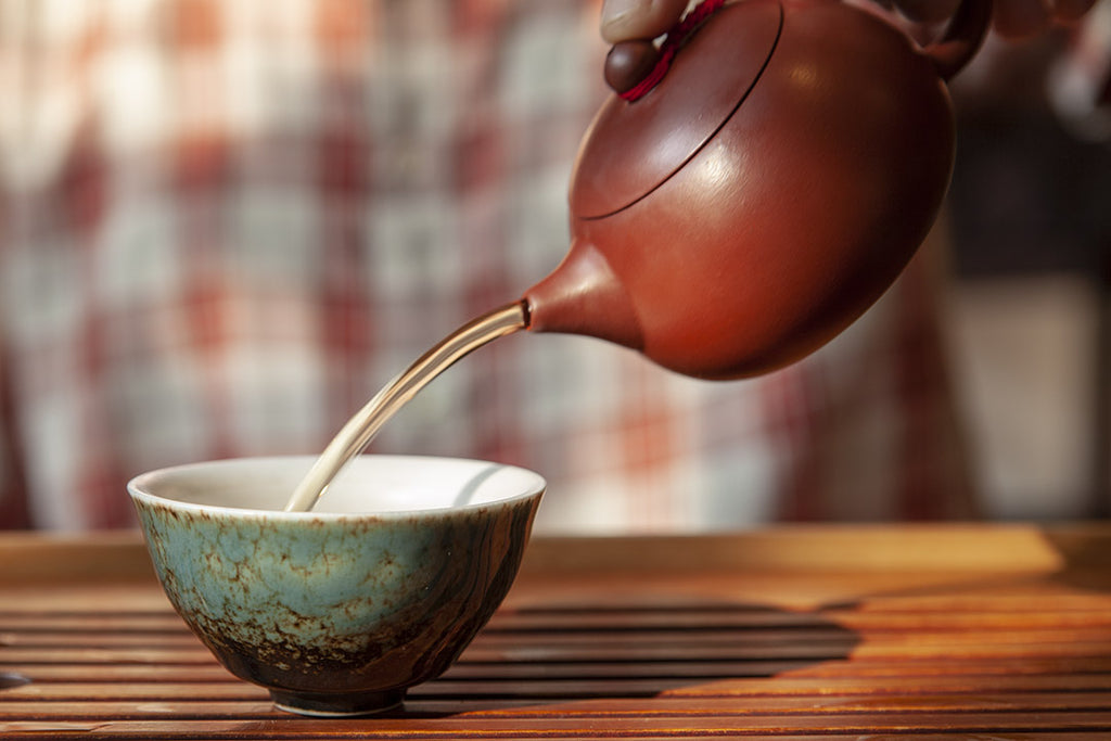 Pouring a cup of oolong tea into a blue teacup