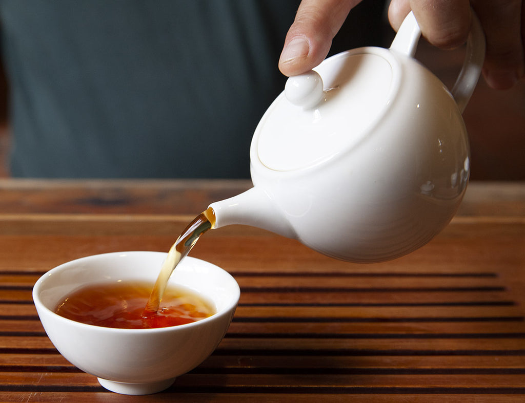 Pouring tea from a teapot into a tea cup