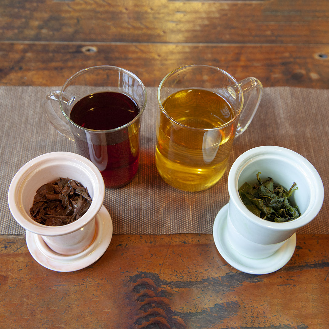 Glass brew mugs with brewed tea and leaves in strainer