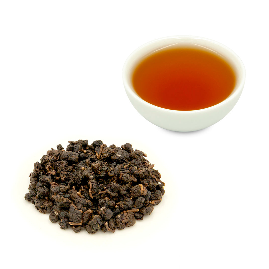 Charcoal Roasted High Mountain Oolong Tea, brewed in a teacup behind some dry tea leaves