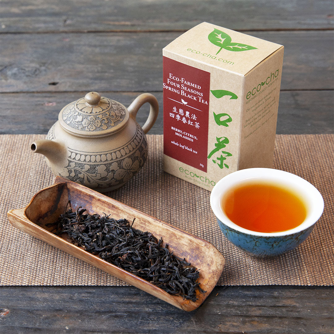 Eco-Farmed Four Seasons Spring Black Tea brewed in a cup and with dry leaves and packaging on a wooden table.
