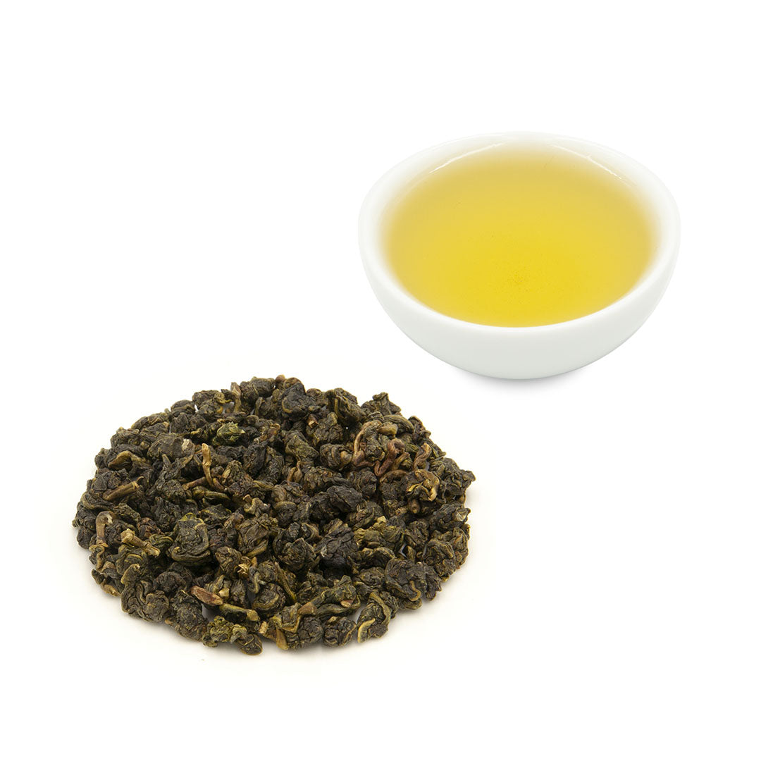 Eco-Farmed Four Seasons Spring Oolong Tea by Eco-Cha Teas brewed in a cup alongside a pile of dry, rolled, tea leaves.