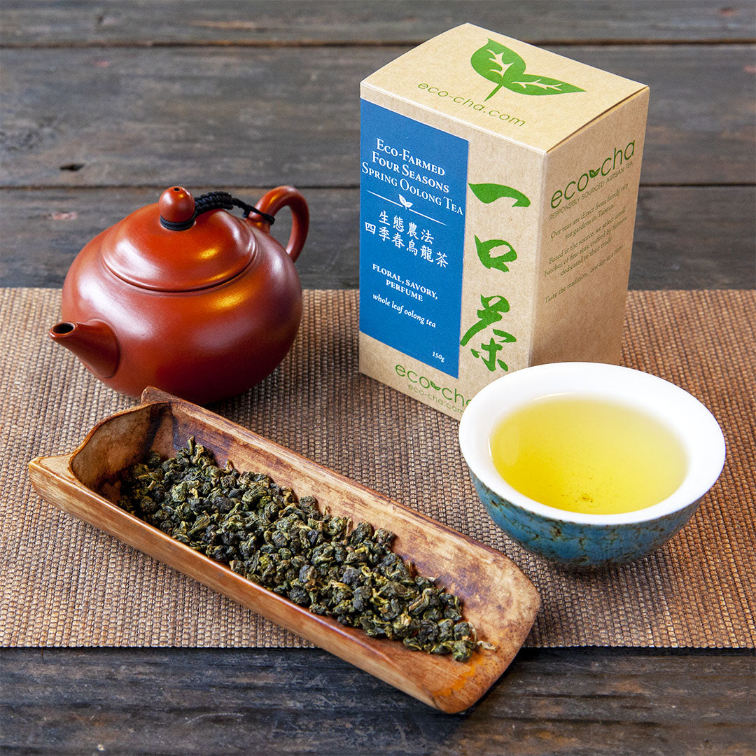Eco-Farmed Four Seasons Spring Oolong Tea, brewed tea in cup alongside dry leaves, packaging and a red teapot.