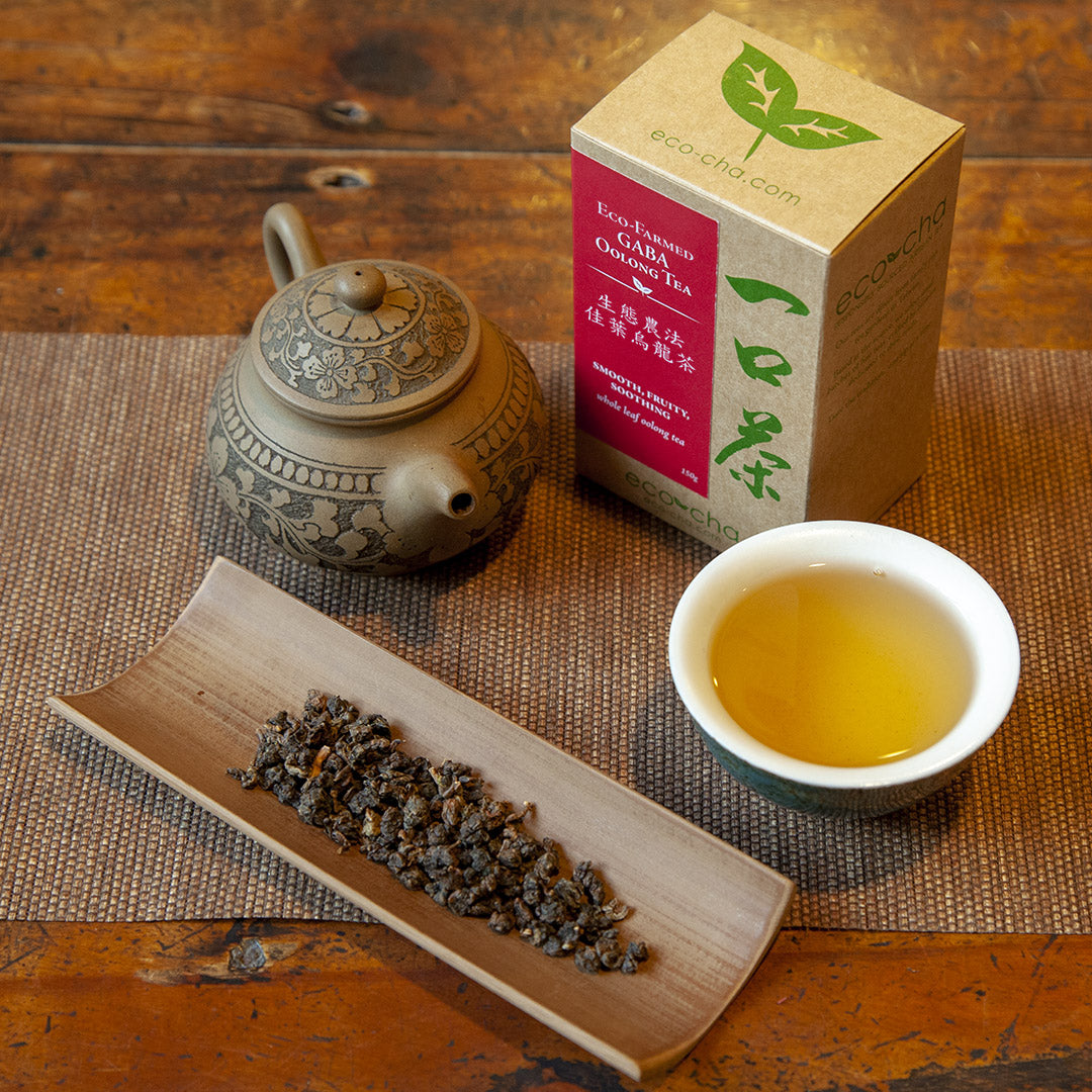 Eco-Farmed GABA Oolong Tea in a cup on a wooden table next to dry leaves and a teapot and a box