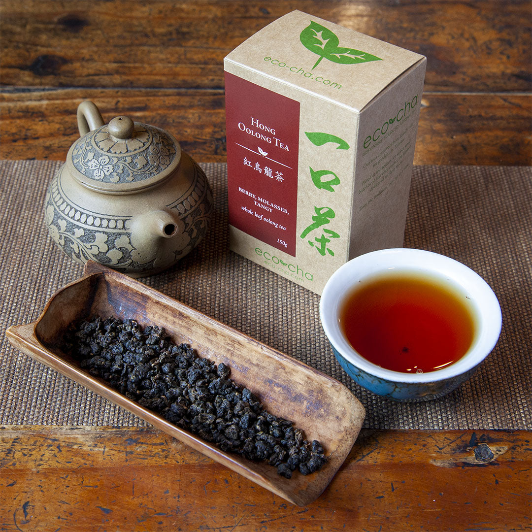 Hong Oolong Tea, dry leaves in a scoop next to brewed tea in a cup alongside package box and teapot