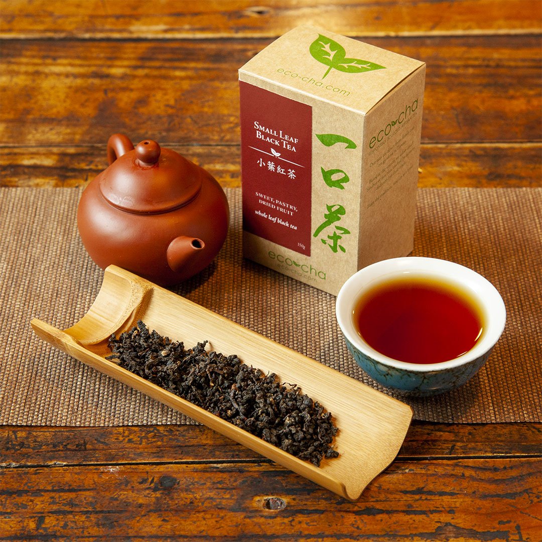 Small Leaf Black Tea in teacup on table with packaging and dry leaves