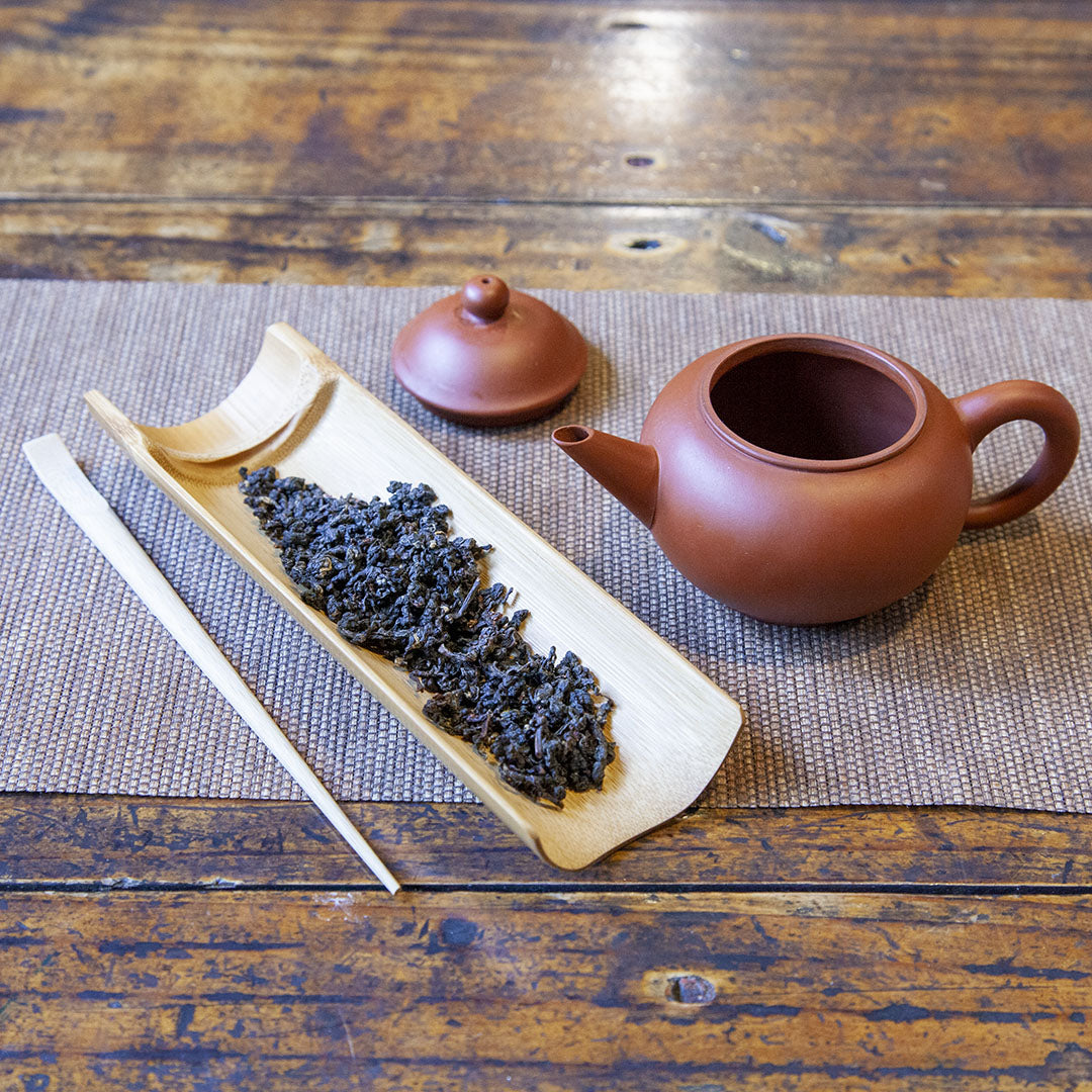 Bamboo tea scoop and tea pick next to teapot