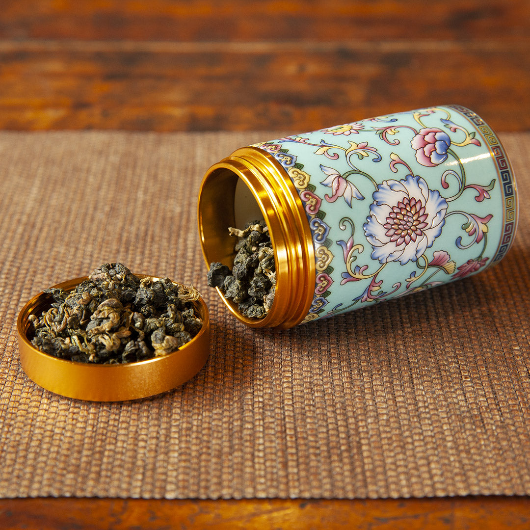 Blue ceramic travel tea caddy with tea leaves
