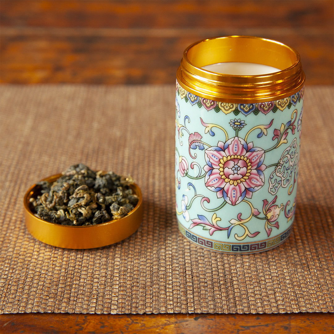 Yellow ceramic tea caddy with tea leaves in cap