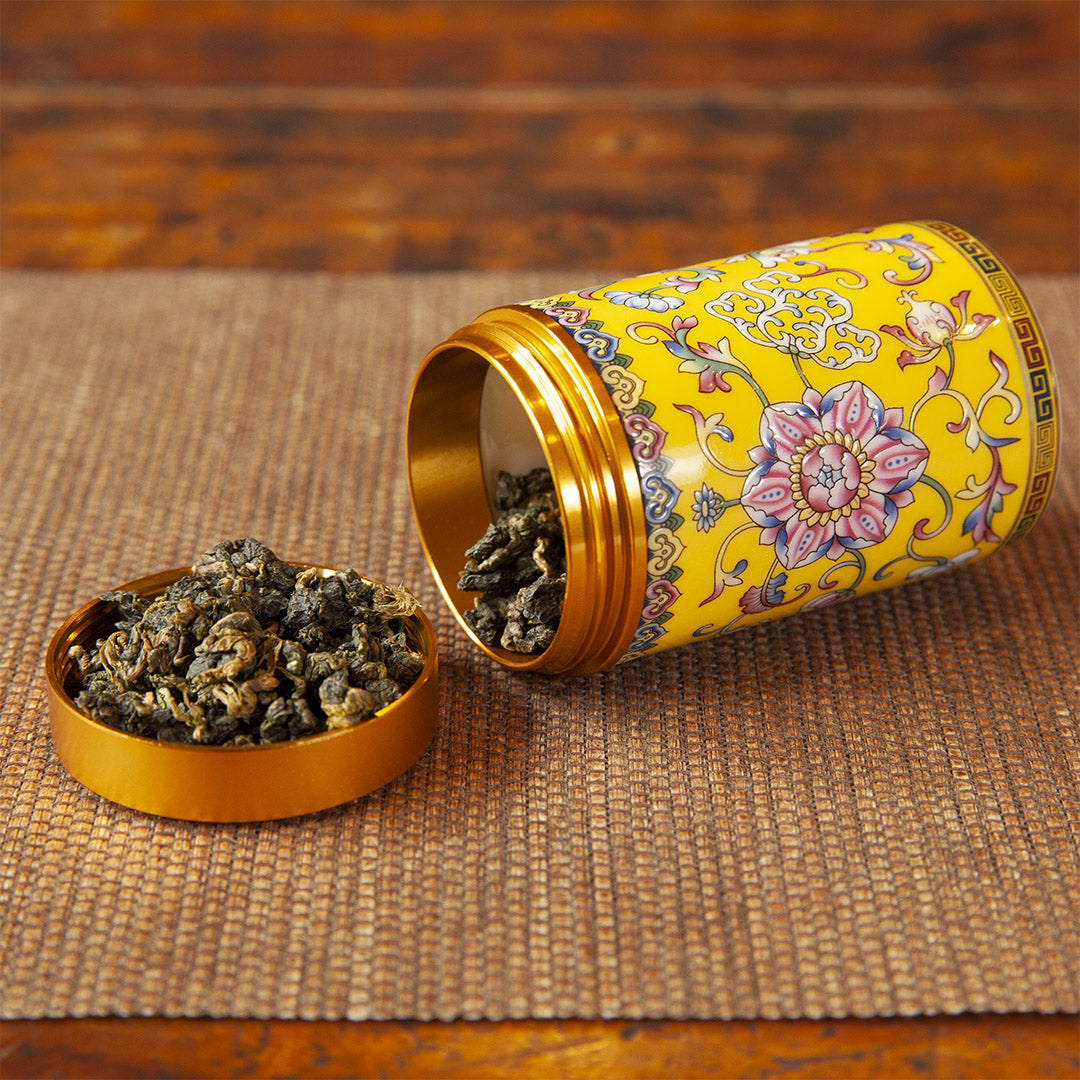 Yellow ceramic travel tea caddy with tea leaves