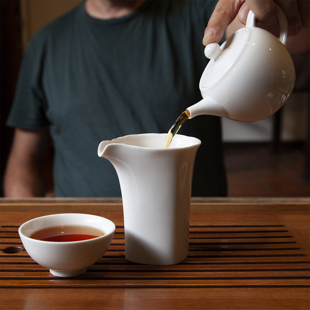 Pouring tea into white porcelain tea pitcher