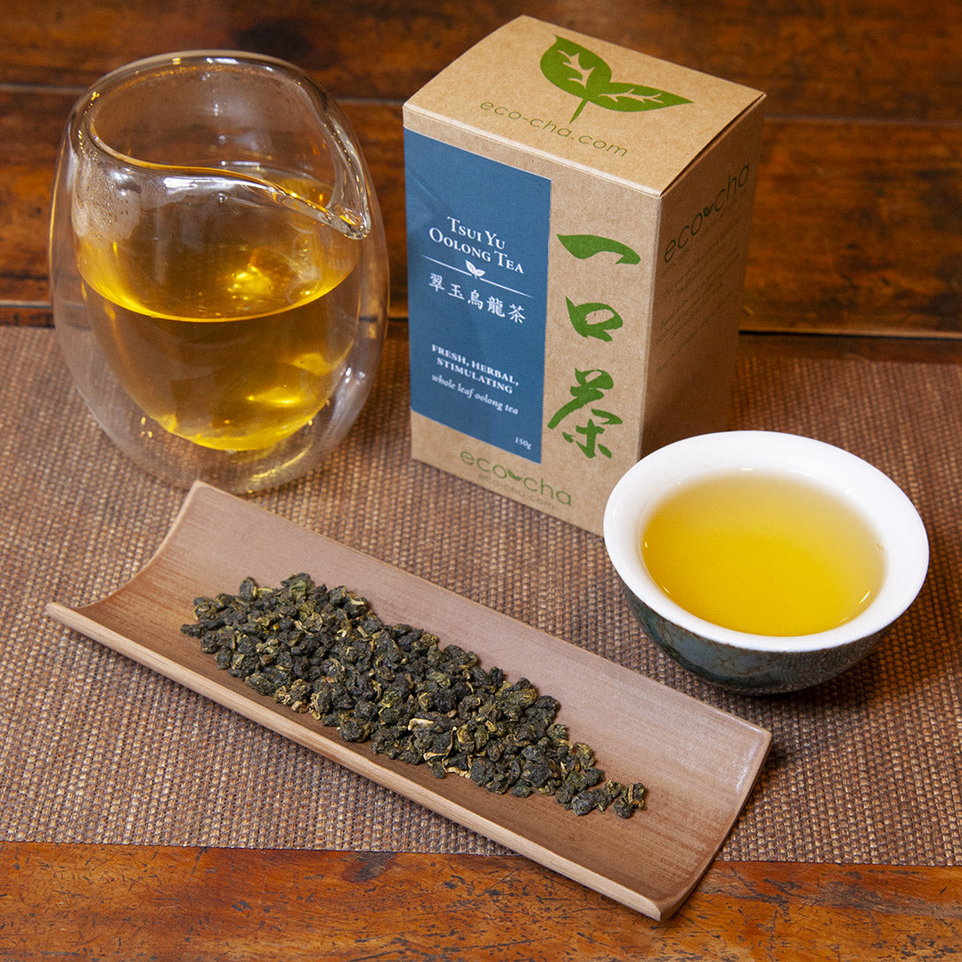 Tsui Yu Oolong Tea in a teacup on a wooden table next to dry tea leaves, a pitcher of tea, and a box