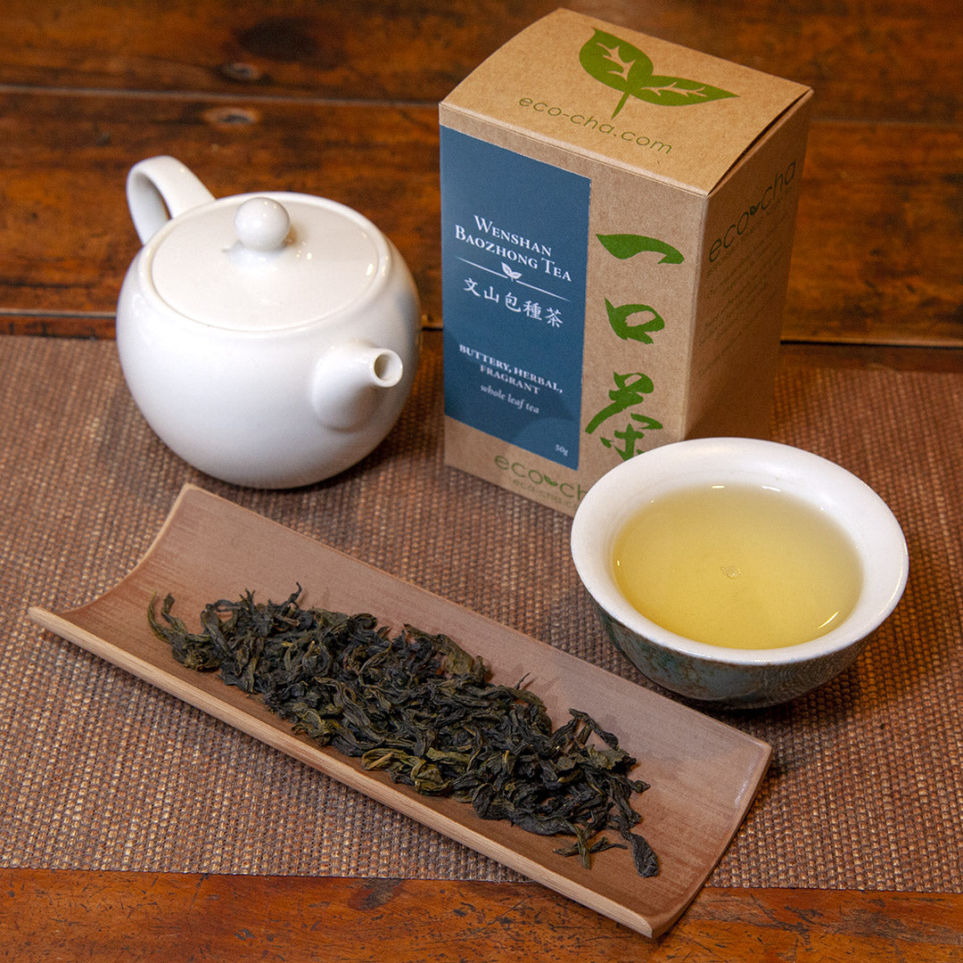 Wenshan Baozhong Tea in a teacup on a wooden table next to dry tea leaves and a white teapot and box
