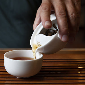 Pouring tea from the single brew teapot into the cup