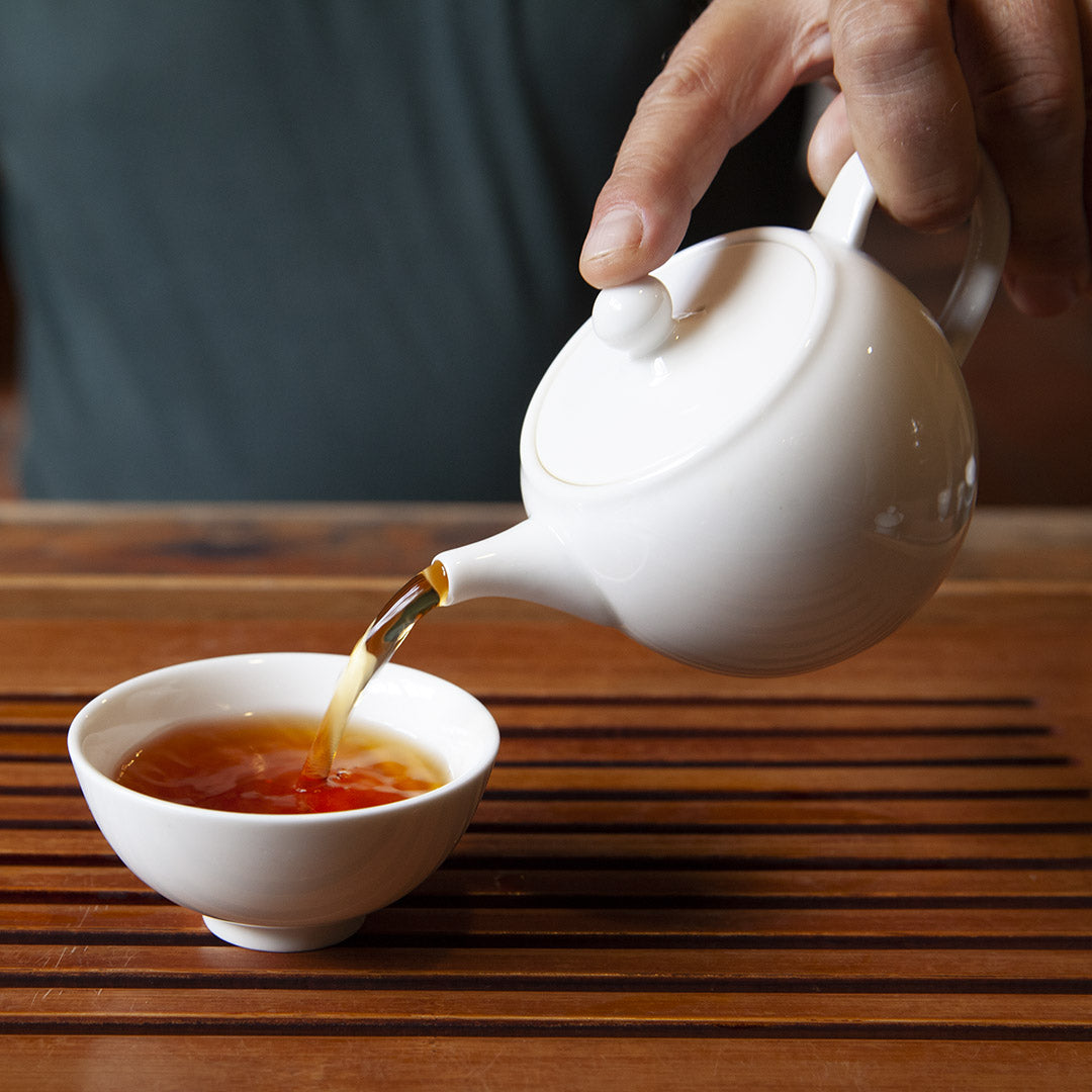 Pouring tea with white porcelain gong-fu teapot into white cup
