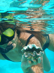 brown skinned lady snorkeling with clam shell
