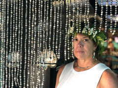 lady with flower crown on her head standing in front of a black pearl curtain