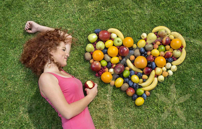 Woman laying on grass with whole foods, embracing the 7 principles of health