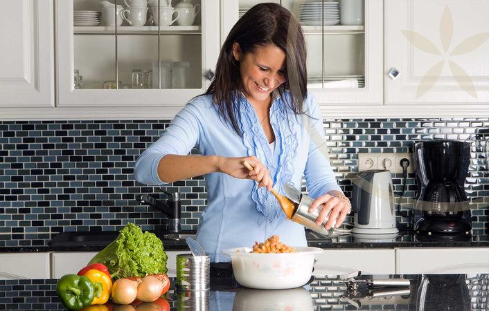 Woman quickly preparing healthy plant-based recipes with vegetables in kitchen