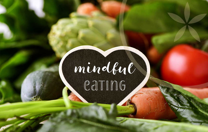 Mindful eating on a heart-shaped sign, surrounded by plant whole foods