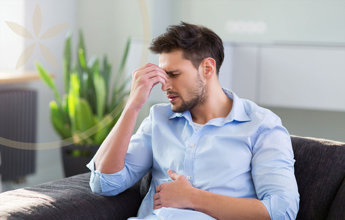 Man holding head, under stress and experiencing gut health issues