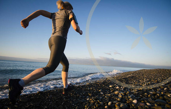Woman running on beach with high energy levels after eating superfoods