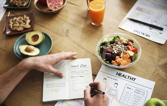Person making healthy food diet plan on table with whole foods and fresh juice