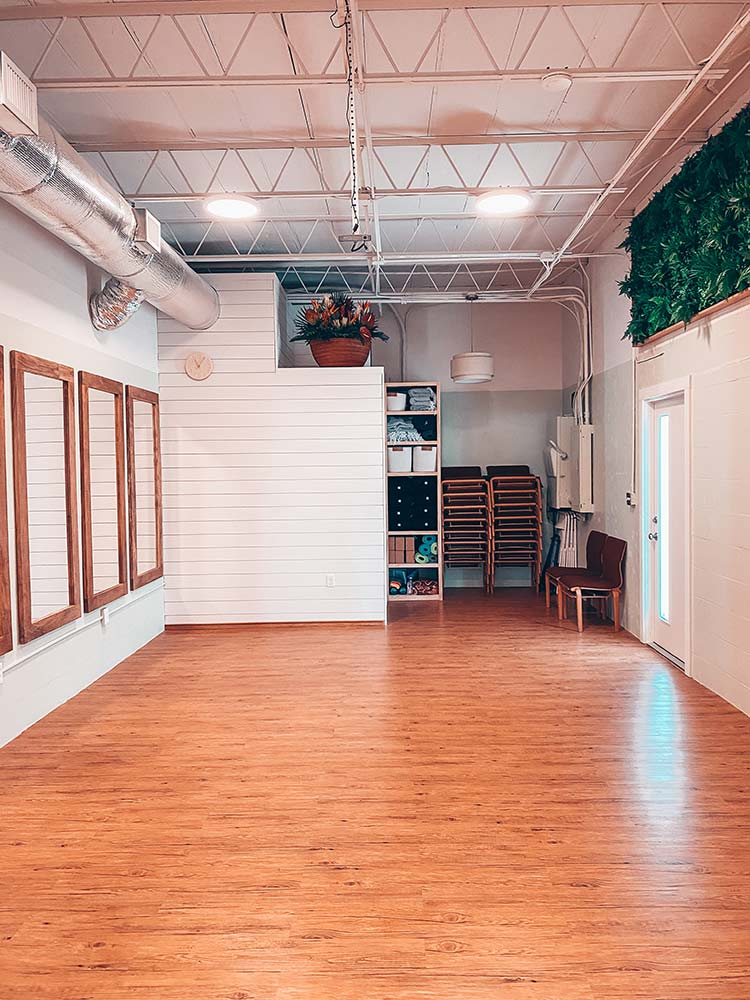 sarasota yoga studio - studio 3, wooden mirrors hanging on the left wall, greenery hanging on the right wall, yoga props positions in the back of the yoga studio