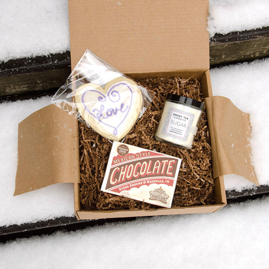 Featuring an exclusive handmade, iced sugar cookie from Cynthia Tobin (Baker and Batcher), Sweet Tea Candles Sugar scented candle, and a cinnamon chili chocolate bar, a spicy little number from Olive & Sinclair Chocolate Co